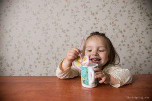Двухлетняя девочка балуется с коктейльной трубочкой и водой